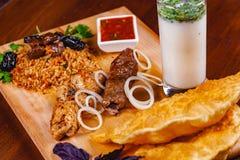 середина кухни восточная Pasties, kebabs, pilaf, ayran на деревянной разделочной доске стоковое изображение rf