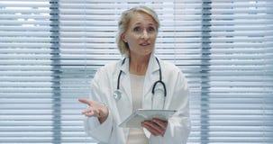 Середина постарела женский доктор используя планшет и говорить к камере 4k видеоматериал