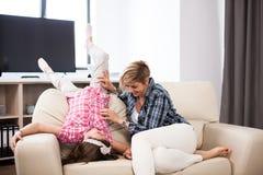 Середина постарела женщина на кресле с ее дочь-подростком Стоковые Изображения