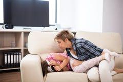 Середина постарела женщина на кресле с ее дочь-подростком Стоковые Фотографии RF