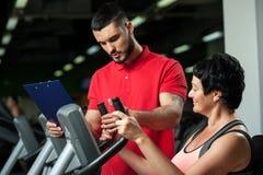 Середина постарела женщина разрабатывая с тренером в спортзале Стоковые Изображения