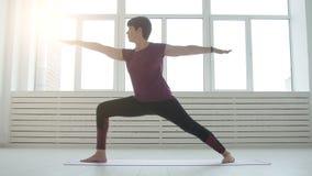 Середина постарела йога привлекательной женщины yogi практикуя внутри помещения сток-видео