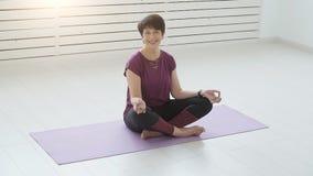 Середина постарела йога привлекательной женщины yogi практикуя внутри помещения акции видеоматериалы