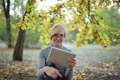 Середина постарела кавказская женщина сидит самостоятельно на золотом парке осени с планшетом, усмехаясь Случайная носка, стекла  стоковое фото
