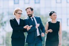 Середина постарела многонациональные предприниматели идя совместно и говоря в городе Стоковая Фотография