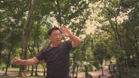 Середина постарела раннее утро разминки kata боевых искусств азиатского японского человека практикуя на парке KLCC