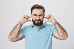 Середина постарела человек закрывая его уши с пальцами Бородатая крышка отца его уши для того чтобы не услышать как его рояль pla стоковая фотография rf