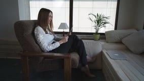 Середина - постаретая женщина говоря на таблетке и эмоционально жестикулирует дома акции видеоматериалы