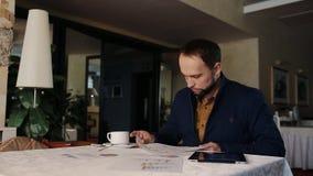 Середина постарела бизнесмен работая на таблетке в кофейне акции видеоматериалы