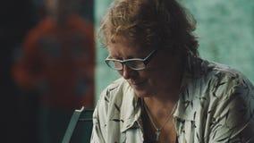 Середина постарела женщина в стеклах сидя в толпить месте, смотря вниз сток-видео