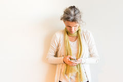 Середина постарела женщина при серые волосы смотря вниз на умном телефоне Стоковое Изображение