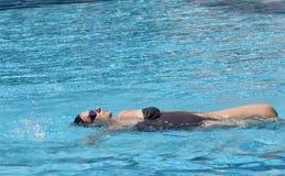 Середина постарела заплывание беременной женщины в бассейне курорта для того чтобы ослабить стоковая фотография rf