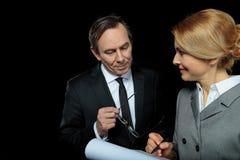 Середина постарела контракт бизнесмена и коммерсантки подписывая на черноте Стоковое фото RF