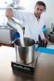 Середина постарела мужской профессионал с сахаром белого пальто лаборатории лить стоковая фотография