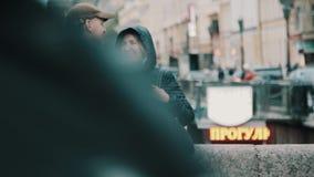Середина постарела пары стоя на мосте в движении пешеходов часа пик города сток-видео