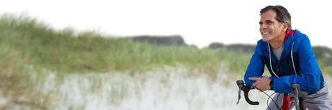 Середина постарела склонность человека на велосипеде против песчанной дюны Стоковая Фотография