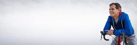 Середина постарела человек на велосипеде против белой стены Стоковое Фото