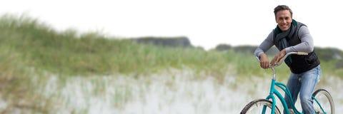 Середина постарела человек на велосипеде против песчанной дюны Стоковые Фото