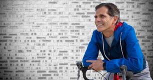 Середина постарела человек на велосипеде против серой кирпичной стены Стоковая Фотография RF