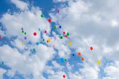 Серии красочных воздушных шаров летая на облачное небо Стоковые Фото