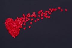 Серии маленьких красных сердец летая на черную предпосылку Стоковое Фото
