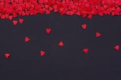 Серии маленьких красных сердец на верхней части на черной предпосылке Стоковое Изображение RF