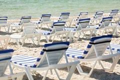 Серии loungers солнца на пляже около моря Стоковая Фотография