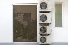 Серия кондиционеров воздуха висит рядом с стеной около окна стоковые изображения rf
