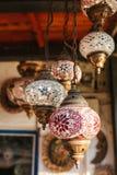 Серия красивых стеклянных фонариков металла висит на предпосылке запачканных декоративных элементов Стоковое Изображение RF