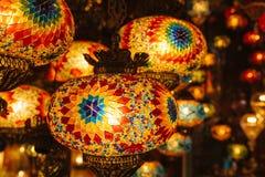 Серия красивых стеклянных фонариков металла висит на предпосылке запачканных светов стоковые изображения