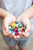 Серия пестротканых конфет в руках ребенка Стоковое Изображение RF