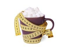 Серия сахара водит к тучности и диабету Чашка кофе или чай верхняя вполне кубов сахара и обернутая в желтой измеряя ленте Стоковое Изображение RF
