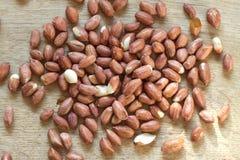 Серия сырцовых плодоовощей арахиса разбросала на деревянную поверхность Стоковая Фотография
