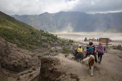 Серия туриста ехать лошадь в кратер держателя Bromo ` s Индонезии Стоковое фото RF