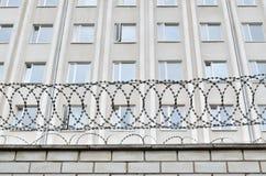 Серое здание огражено с колючей проволокой Символ диктаторского и авторитарного режима стоковое фото rf
