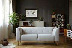 Серое кресло в винтажном интерьере живущей комнаты с деревянными кухонным шкафом, плакатом и заводом Реальное фото стоковое фото