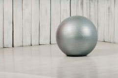 Серое fitball в спортзале, светлом поле и предпосылке Стоковая Фотография RF
