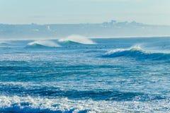 Серферы ждать волны занимаясь серфингом Стоковые Изображения