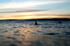 Серферы ждать волны как комплекты Солнця Стоковые Фото