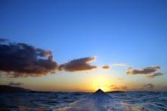 серферы захода солнца Гавайских островов занимаясь серфингом взгляд Стоковые Изображения