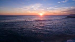 Серферы на волнах в вечере на виде с воздуха захода солнца Стоковое фото RF