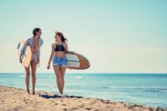 Серферы на пляже имея потеху в лете Маленькие девочки с прибоем b стоковые фотографии rf