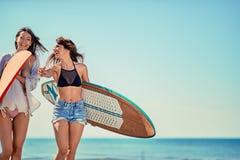 Серферы на пляже имея потеху в лете Маленькие девочки с прибоем b стоковая фотография