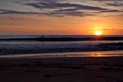 Серферы на пляже Санты Терезы на заходе солнца/Коста-Рика Стоковое Фото