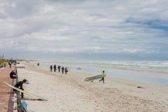 Серферы получая готовый пойти вне в море стоковое изображение rf