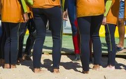 Серферы слушают к их тренеру на пляже Стоковые Изображения