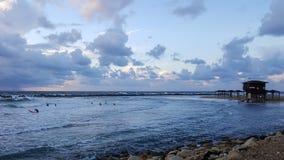 Серферы silhouetted с красочной предпосылкой неба и моря Стоковое Изображение