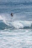 Серфер в бурных морях плавает на голубой океанской волне на пляже Uluwatu, Бали Стоковые Фотографии RF