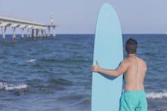Серфер держа его голубой surfboard от позади Стоковое фото RF