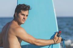 Серфер держа его голубой surfboard Стоковое фото RF